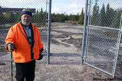 Tour guide Ron Bell opens the convict-built fence that surrounds the petroforms.