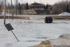 A pickup truck drives through water on Red River Drive, south of Winnipeg on Saturday.