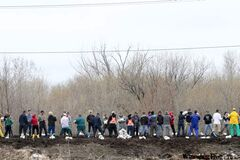 Volunteers hoist sandbags to help stabilize aqua dams on the dike along the south side of the Assiniboine River on Monday.