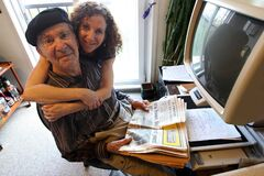 Val Werier receives a hug from his daughter, Judy, while seated at a computer and holding a copy of the Winnipeg Tribune.