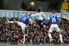 Tottenham's Paulinho, centre, heads the ball with Everton's Leon Osman, left, during their English Premier League soccer match between Tottenham Hotspur and Everton at the White Hart Lane stadium in London, Sunday, Feb. 9 2014. (AP Photo/Alastair Grant)
