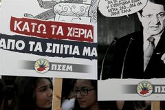 Demonstrators hold banners, left, reading in Greek