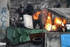 Protesters clash with police in central Kiev, Ukraine, Monday, Jan. 20, 2014. Protesters erected barricades from charred vehicles in central Kiev as the sound of stun grenades pierce the freezing air, after a night of rioting sparked by the passage of laws aimed at curbing street protests. (AP Photo/Sergei Chuzavkov)