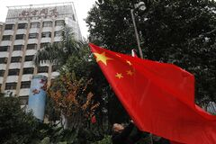 A leftist raises a Chinese national flag during a counter-protest against supporters of the Southern Weekly newspaper outside the headquarters of the newspaper in Guangzhou, Guangdong province, China Wednesday, Jan. 9, 2013. Communist Party-backed management and rebellious editors at the influential weekly newspaper have defused a high-profile standoff over censorship that turned into a test of the new Chinese leadership's tolerance for political reform. (AP Photo/Vincent Yu)