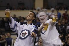 Winnipeg Jets fans enjoy cold glasses of beer during a game at the MTS Centre.