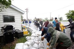 Members of the community join together in Brandon to sandbag.