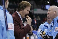 Glenn Howard shares a doughnut with Ron Burgundy following the opening ceremonies at the 2013 Roar Of The Rings championship in Winnipeg.