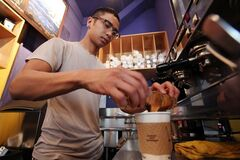 In this photo taken April 19, 2012, a barista prepares a two-shot coffee drink in a coffee shop in Seattle. THE CANADIAN PRESS/AP, Elaine Thompson)
