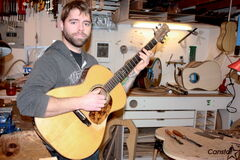 The Duhks guitarist and North Kildonan luthier Jordan McConnell is shown in his shop. McConnell is holding his first-ever project, which he constructed over a decade ago.