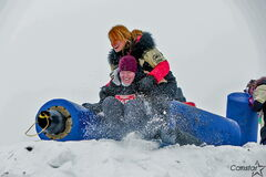 "An Ice Donkey racer is tackled at the ""king of the castle"" obstacle by a volunteer member of the Manitoba Fearless women's football team."