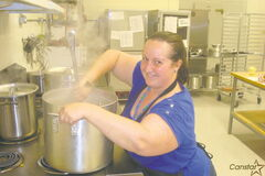 Jennifer Laviolette prepares some hot food for youngsters as part of the Lunch Lady crew.