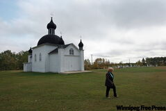 Longtime parishioner Kay Balak walks across the yard of the Holy Trinity Ukrainian Catholic Church in Grifton, west of Dauphin.