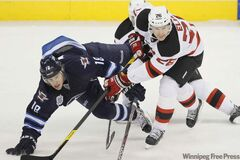 New Jersey Devils forward Patrik Elias (26) takes out Winnipeg Jets forward Bryan Little (18) during first period NHL action in Winnipeg on Saturday.