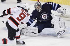 Winnipeg Jets goaltender Ondrej Pavelec saves the shot from New Jersey Devils' Bobby Butler during the first-period.