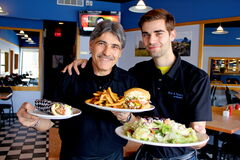 Gus and Tony Vailas show off some signature dishes: homemade souvlaki gyro, deluxe cheeseburger and fries, and a Greek salad. Their restaurant, Gus & Tony's at the park, opened at the start of 2013.