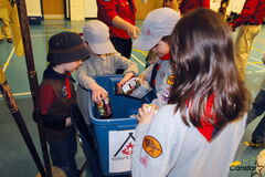 Cubs, and a Beaver, do a good turn for the hungry by putting food in a bin for Winnipeg Harvest.