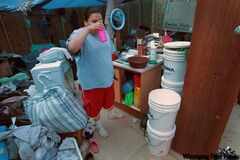 Vivian Flett gets a drink of water in her temporary home -- a plywood-and-­tarp shack the family was forced to live in all summer while waiting for plumbing to be installed in their home.