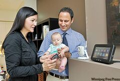 Anthony Antonelli, a Rogers employee, and his family test features of Smart Home Monitoring from Rogers, which allows consumers to control household devices from a smartphone or computer.