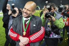 Bayern's Franck Ribery of France, obscured, hugs Bayern head coach Pep Guardiola of Spain, front, after winning the German Soccer Cup Final between FC Bayern Munich and Borussia Dortmund at the Olympic Stadium in Berlin, Germany, Saturday, May 17, 2014. (AP Photo/Gero Breloer)