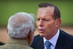 Australian Prime Minister Tony Abbott, right, speaks to his Indian counterpart Narendra Modi during his ceremonial reception in New Delhi, India, Friday, Sept. 5, 2014. Abbott is on a two-day visit to India. (AP Photo/Saurabh Das)