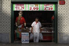 A butcher, holding bags, steps out of a butcher's shop next to a mannequin dressed in a Portugal's national soccer colors in Lisbon, Wednesday, Aug. 21, 2013. Portugal raised 1 billion euros ($1.34 billion) in an auction of short-term debt Wednesday amid signs the country's deep recession has bottomed out, though investors remain wary of the political and economic risks of planned new austerity measures. (AP Photo/Francisco Seco)