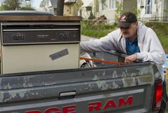 Pat Hilton secures a dishwasher to a truck after finding it on the curb along Arlington Street Saturday morning. Saturday and Sunday is giveaway weekend, when residents put free items on their curbs for the picking.