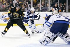 Bruins winger Brad Marchand tries to get a shot off on Jets goalie Ondrej Pavelec as Paul Postma defends during the second period Monday. Marchand's first-period marker tied the game.