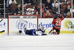 Winnipeg Jets goalie Ondrej Pavelec dives to make a save as New Jersey Devils' Patrik Elias slides by during an NHL game in Newark, N.J., Sunday. The Jets lost 3-2 in OT.