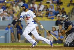 Los Angeles Dodgers' Matt Kemp, left, hits an RBI single to win the game as Atlanta Braves catcher Evan Gattis looks on during the 10th inning of a baseball game, Wednesday, July 30, 2014, in Los Angeles. (AP Photo/Mark J. Terrill)