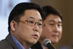 Daum Communications Corp. CEO Choi Sae-hoon, left, answers a reporter's question as Kakao Corp. CEO Sirgoo Lee listens during their press conference in Seoul, South Korea, Monday, May 26, 2014. Mobile messenger service Kakao Talk is seeking a backdoor listing on the South Korean stock exchange by combining with the country's second largest Internet portal. (AP Photo/Lee Jin-man)