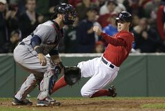 Boston Red Sox's Brock Holt beats the throw to score as Cleveland Indians catcher Yan Gomes waits for the ball on a double by Dustin Pedroia during the seventh inning of a baseball game at Fenway Park in Boston, Friday, June 13, 2014. (AP Photo/Charles Krupa)
