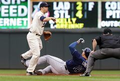 Tampa Bay Rays' James Loney is forced at second by Minnesota Twins' second baseman Brian Dozier on a double play hit into by Logan Forsythe during the fourth inning of a baseball game, Saturday, July 19, 2014, in Minneapolis. (AP Photo/Jim Mone)