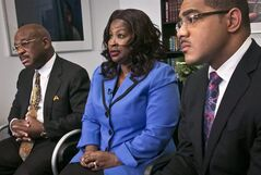 Cynthia Robinson is flanked by her attorneys Willie Gary, left, and Christopher Chestnut, right, as she speaks during an interview, Monday, July 21, 2014 in New York. R.J. Reynolds Tobacco Co., the No. 2 U.S. cigarette maker, is vowing to fight a jury verdict of $23.6 billion in punitive damages in a lawsuit won by Robinson on behalf of of her late husband, Michael Johnson Sr., who died of lung cancer. (AP Photo/Bebeto Matthews)