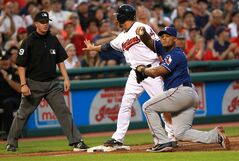 Texas Rangers' Adrian Beltre, right, signals to the dugout as Cleveland Indians Mike Aviles asks for time from third base umpire Corey Blaser in the fourth inning of a baseball game Friday, Aug. 1, 2014, in Cleveland. Aviles was ruled out after a video review. (AP Photo/Aaron Josefczyk)