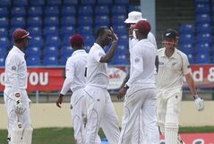 West Indies bowler Kemar Roach, center, celebrates with teammates after taking the wicket of New Zealand's Mark Craig who was caught behind by West Indies' Denesh Ramdin for 67 runs during the second innings on the last day of their second cricket Test match in Port of Spain, Trinidad, Friday, June 20, 2014. (AP Photo/Arnulfo Franco)