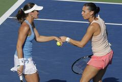 Martina Hingis, left, pumps fists with Flavia Pennetta during a semifinal doubles match against Cara Black and Sania Mirza at the 2014 U.S. Open tennis tournament, Thursday, Sept. 4, 2014, in New York. (AP Photo/Charles Krupa)