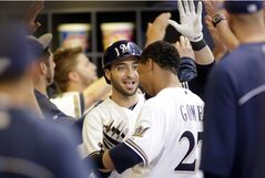 Milwaukee Brewers' Ryan Braun, center, celebrates with teammate Carlos Gomez (27) after hitting a two-run home run against the Pittsburgh Pirates during the first inning of a baseball game Friday, Aug. 22, 2014, in Milwaukee. (AP Photo/Darren Hauck)