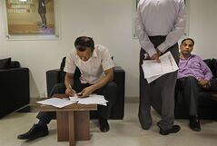 In this Tuesday, March 26, 2013 photo, a salaried Indian, left, fills in his income tax paper as others wait for their turn to submit their papers at Income Tax office in New Delhi, India. In a country of 1.2 billion people, a country where years of staggering economic growth have created tens of thousands of new millionaires annually and a recent slowdown has done little damage to a thriving luxury goods market, far less than .01 percent of the population admits they are in the top tax bracket. Less than 3 percent of Indians file income tax returns at all, and officials say only about 1.5 million taxpayers declare earning more than 1,000,000 rupees per year (about $18,000). (AP Photo /Manish Swarup)