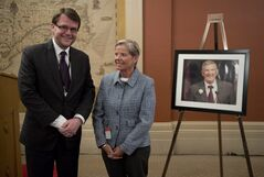 Standing in front of a portrait of Jim Travers, this year's recipient of the Travers Fellowship Mike Blanchfield of the Canadian Press poses with Joan Travers after he was named at a ceremony on Parliament Hill, Wednesday March 20, 2013 in Ottawa. THE CANADIAN PRESS/Adrian Wyld