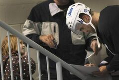 Danica van Leeuwen, 5, gets an autograph from Captain Andrew Ladd today at practice at the MTS Iceplex.