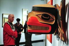 A visitor looks at the wooden sculpture, Killer Whale Transforming into a Thunderbird, by Robert Davidson.