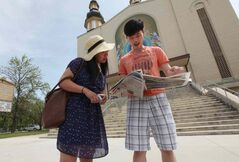 Jenny Yee and Kai Wu check out where else they would like to explore after visiting Ukrainian Orthodox Metropolitan Cathedral of the Holy Trinity on Main Street during the annual Open Doors Winnipeg event Saturday.