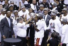 Miami Heat owner Micky Arison hands the Eastern Conference Championship trophy to Greg Oden on Friday, May 30, 2014, in Miami. The Heat defeated the Indiana Pacers 117-92 to advance to the NBA Finals. (AP Photo/Wilfredo Lee)