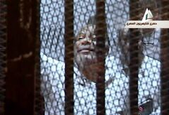In this image taken from Egypt State TV, Muslim Brotherhood lawmaker Saad el-Katatni waves from the defendant's cage in a courtroom in Cairo, Egypt, Tuesday, Jan. 28. 2014. Egypt's toppled President Mohammed Morsi stood inside a glass-encased metal cage on Tuesday, separated from other defendants for the start of a new trial Tuesday over charges from prison breaks during the country's 2011 revolution, state television reported. (AP Photo/Egyptian State TV)