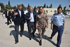 U.S. Secretary of State John Kerry, left, and Jordanian Foreign Minister Nasser Judeh, second left, are escorted by military officers at Marka airport in Amman, Jordan, Thursday, July 18, 2013, before boarding a helicopter bound for the Zaatari refugee camp. Angry Syrian refugees urged Kerry on Thursday to do more to help opponents of President Bashar Assad's government, venting frustration at perceived inaction on their behalf. (AP Photo/Mandel Ngan, Pool)