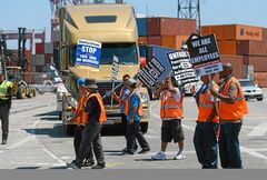 FILE - This July 8, 2014 file photo shows members of the Teamsters Union picketing at the Port of Long Beach, Calif., in support of a strike by port truck drivers. Negotiators seeking to avoid labor unrest at West Coast ports made significant progress with their announcement of a tentative deal on health care benefits, Tuesday, Aug. 26, 2014, a knotty issue that had tied up contract talks for months. (AP Photo/The Daily Breeze, Stephen Carr)