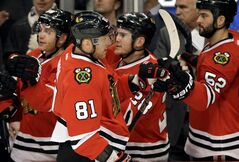 Chicago Blackhawks' Marian Hossa (81) is congratulated by teammates after his goal during the first period of an NHL hockey game against the Anaheim Ducks in Chicago, Friday, Jan. 17, 2014. (AP Photo/Nam Y. Huh)