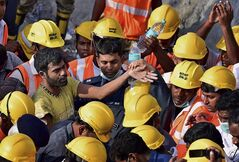 In this Tuesday, July 1, 2014 photograph, India's National Disaster Response Force personnel stand around a man, left, they rescued from beneath the debris of a building that collapsed Saturday on the outskirts of Chennai, India. Rescuers pulled seven more survivors from under the concrete ruins of a collapsed 11-story building on Tuesday, three days after it toppled and killed dozens of people in southern India, officials said. (AP Photo)