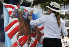 Artist Susan Sommer-Luarca, of Springfield, Mo., paints an image of Triple Crown hopeful California Chrome outside the grandstand at Belmont Park during the undercard races for the Belmont Stakes horse race, Saturday, June 7, 2014, in Elmont, N.Y. (AP Photo/Kathy Willens)