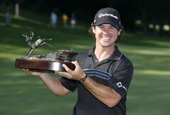 Brian Harman holds the 2014 John Deere Classic trophy after the golf tournament at TPC Deere Run in Silvis, Ill., Sunday, July 13, 2014. (AP Photo/Charles Rex Arbogast)